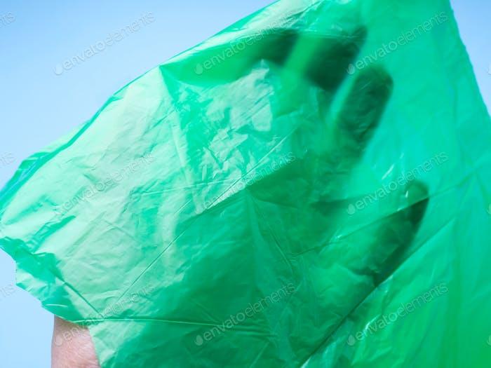 Hand under green plastic bag film