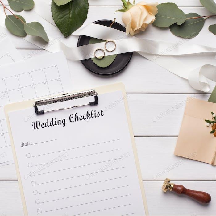 Wedding checklist and accessories on white wooden background
