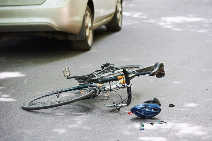 Drunk driving. Bicycle and silver colored car accident on the road at forest at daytime