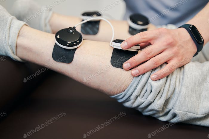 Hand of manual therapist pressing button on stimulation module
