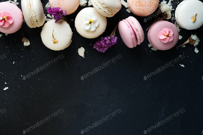 Colorful macarons on black stone background. Top view with copy space