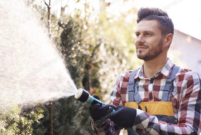 Botanist with garden hose watering flower