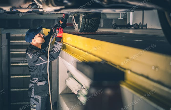 Car Mechanic Performing Vehicle Undercarriage Diagnostic Check