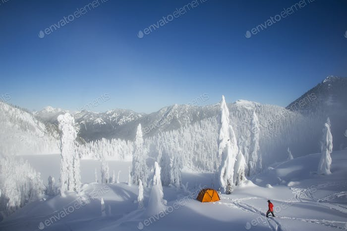 Michael Hanson walks through deep powder to his campsite in snow covered mountains
