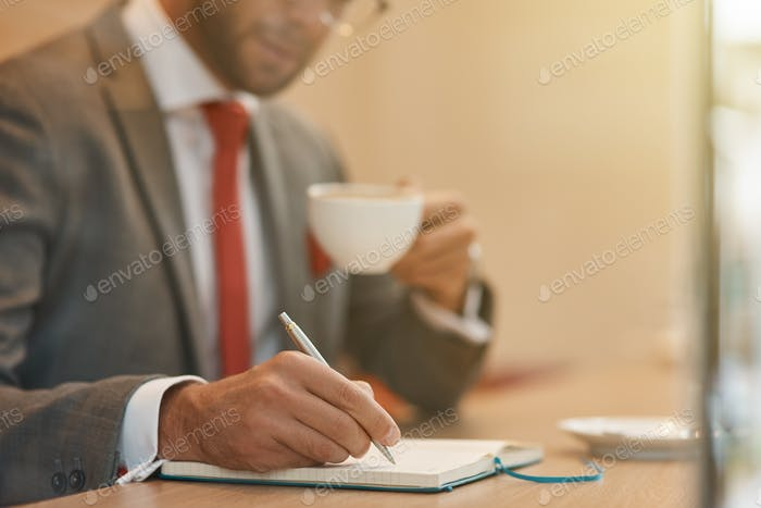 Confident businessman drinking coffee and making notes