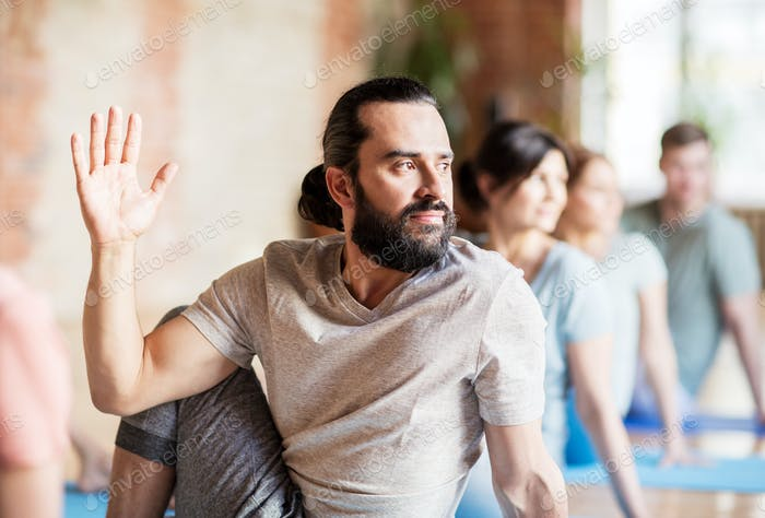 man with group of people doing yoga at studio