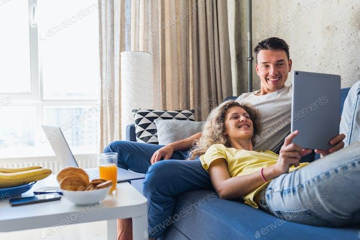 hombre joven y mujer enamorado sentado en casa trabajando en línea