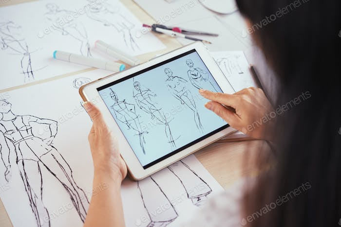 Anonymous tailor scrolling sketches on tablet