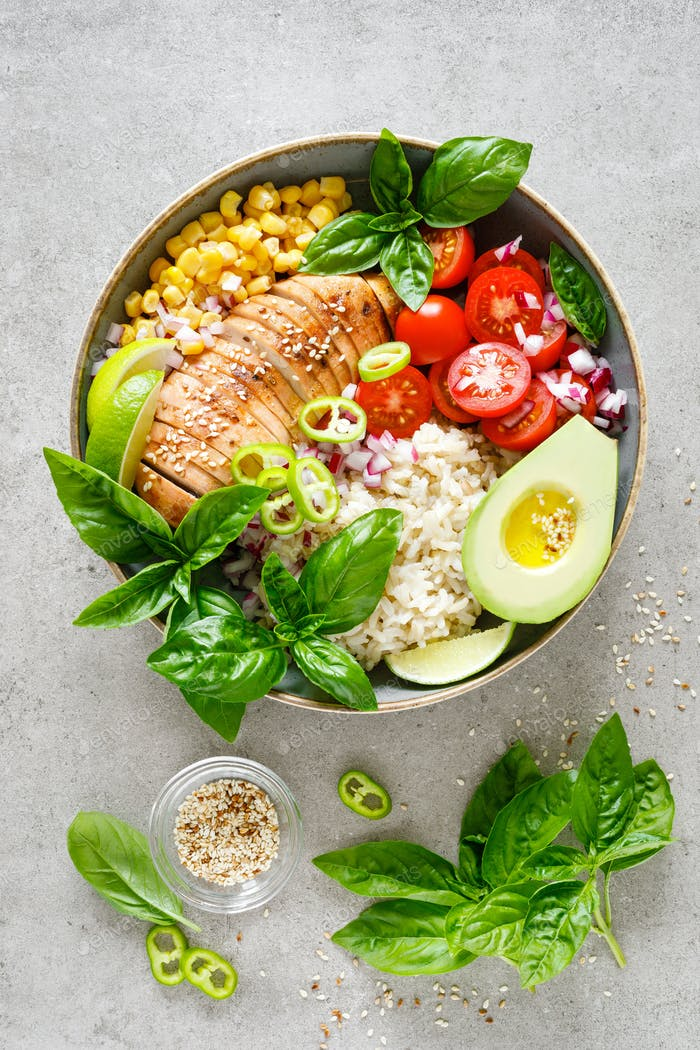 Buddha lunch bowl with grilled chicken breast, tomato, onion, corn, avocado, basil salad and rice