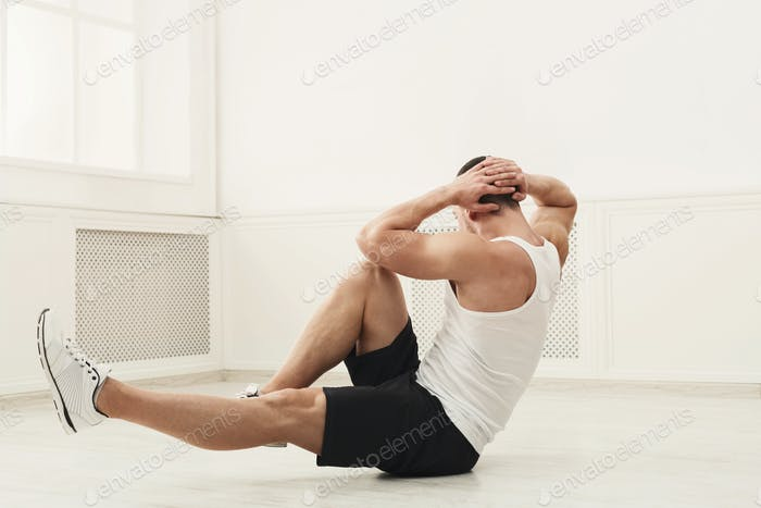Athletic young man doing sit-ups