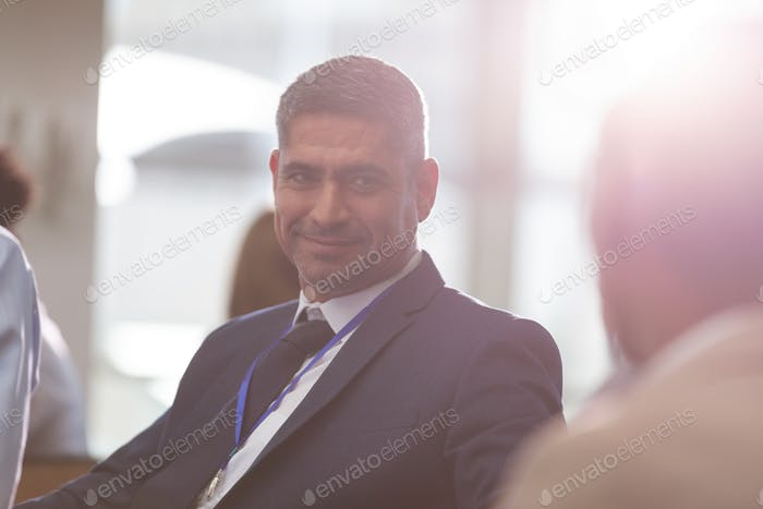 Front view of smiling mixed race businessman looking at colleague during seminar in office building