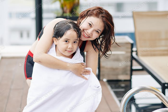 Mother wiping daughter with towel