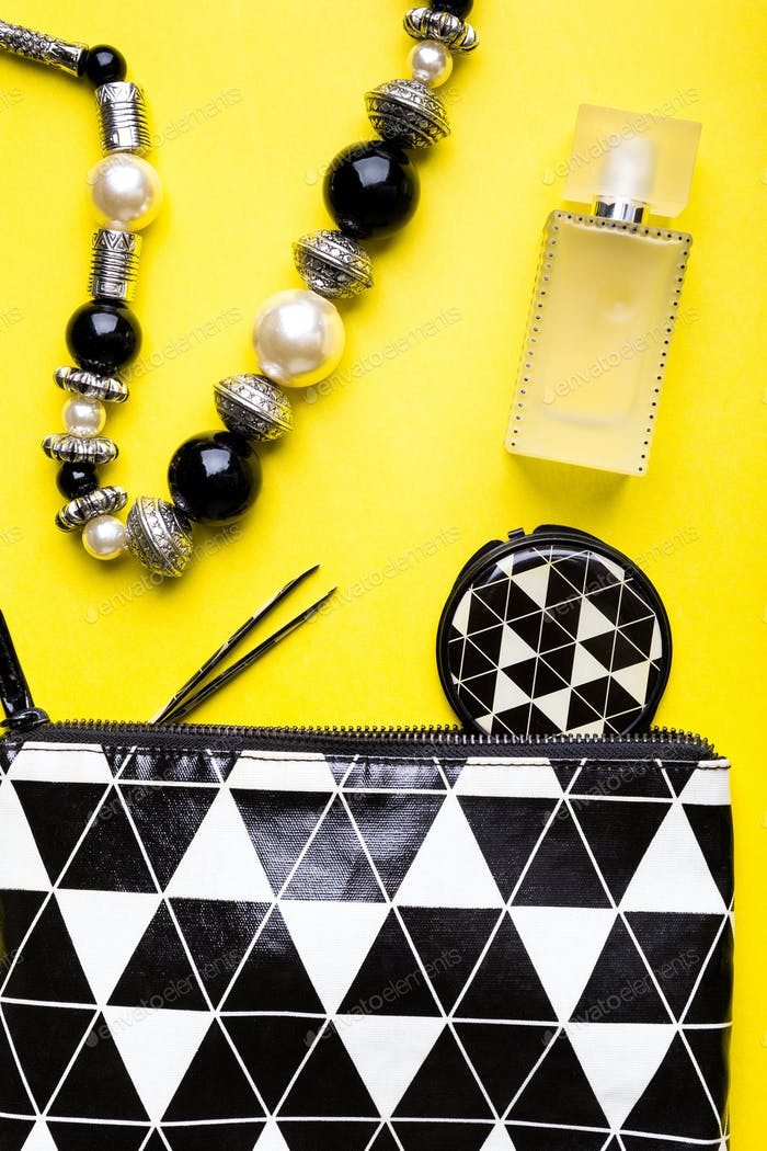 Woman handbag with makeup and accessories on yellow background. Flat lay.