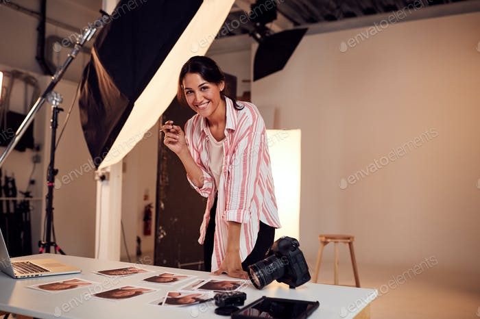 Portrait Of Female Photographer Editing Images From Photo Shoot In Studio