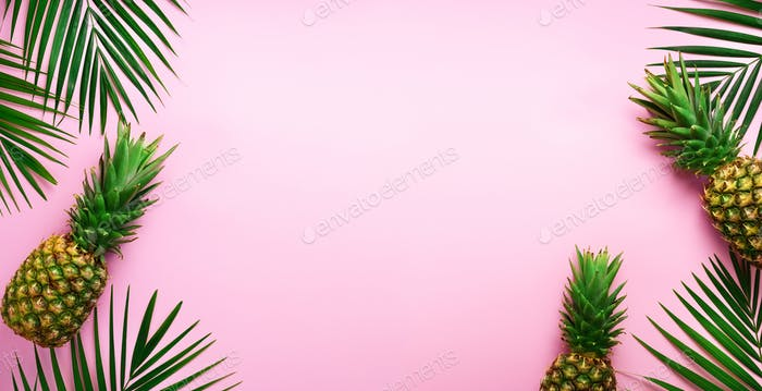 Pineapples and tropical palm leaves on punchy pastel pink background. Summer concept. Creative flat