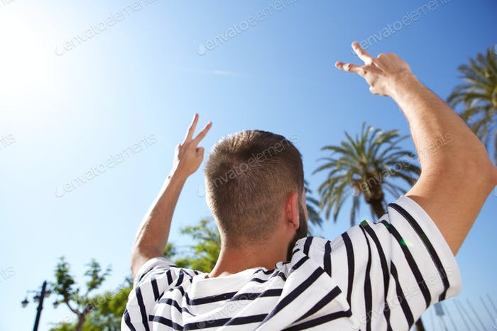 Rear of man with hands outstretched in peace signs