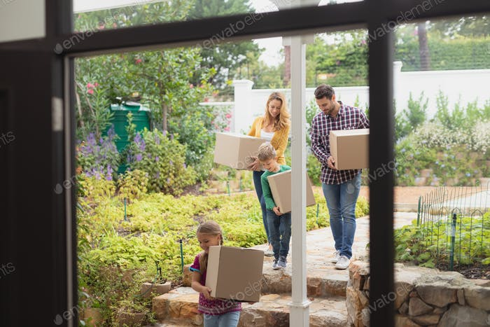 Front view of happy Caucasian family with cardboard boxes walking towards home