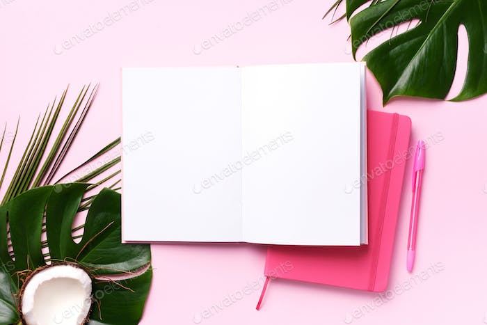 Female blog writer workspace concept. Green monstera palm leaves, coconut on pink background with