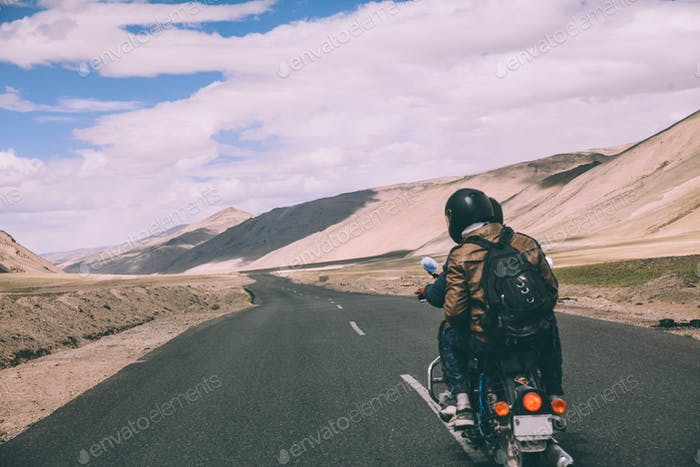 back view of two motorcyclists on mountain road in Indian Himalayas, Ladakh region