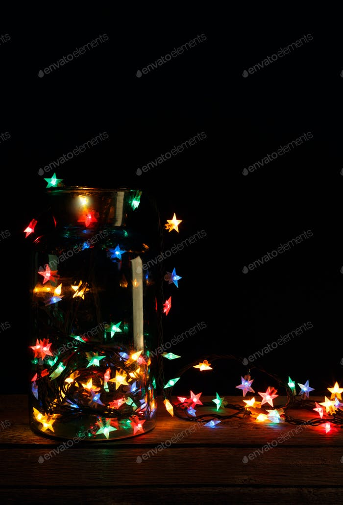 christmas lights in glass jar on wood, holiday background