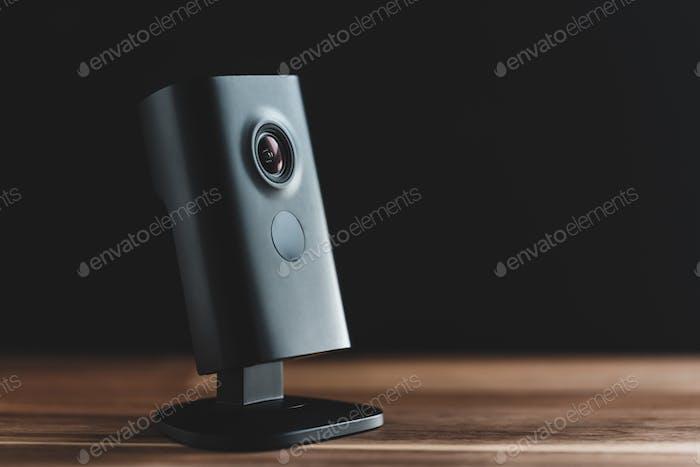 Black minimalist CCTV camera at home on a wooden table.