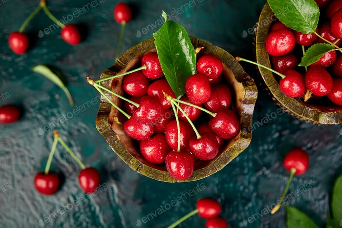 Red cherry in bowl on green background. Summer or spring concept.