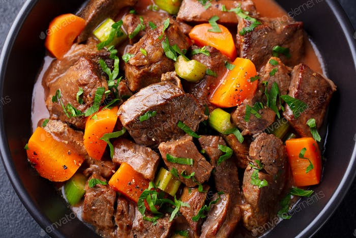 Beef Meat and Vegetables Stew in Black Bowl. Dark Background. Close up.