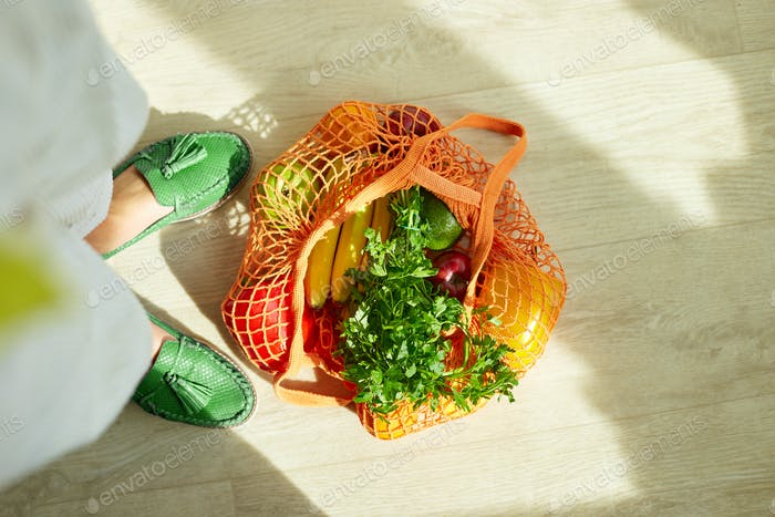 Shopping string grocery reusable mesh bag full of fresh fruits and vegetables on the floor at home