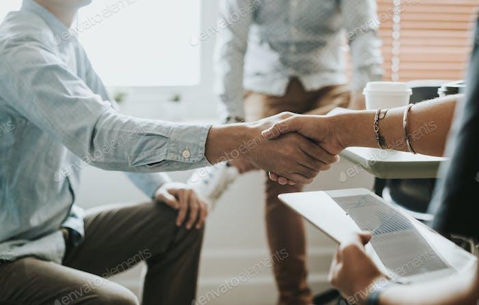 Geschäftsleute in einem Meeting beim Händeschütteln