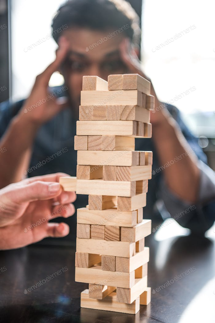 young friends playing jenga game, focus on foreground