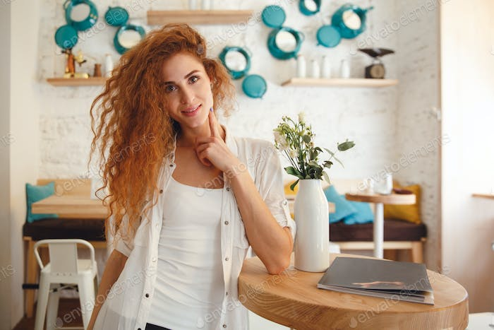 Happy beautiful redhead young lady posing in cafe