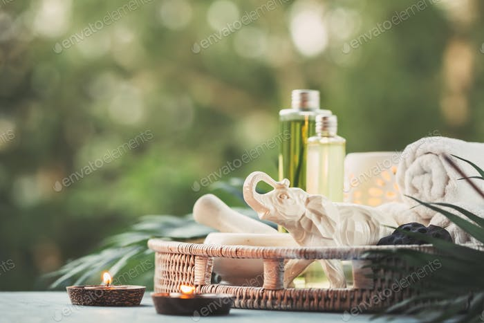 Beautiful composition with natural cosmetic, towels and burning candles.