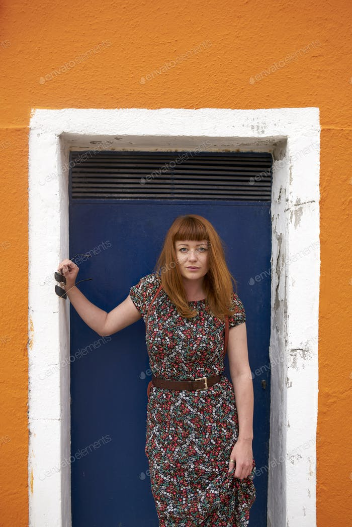 Caucasian redhead woman with floral dress and colorful building