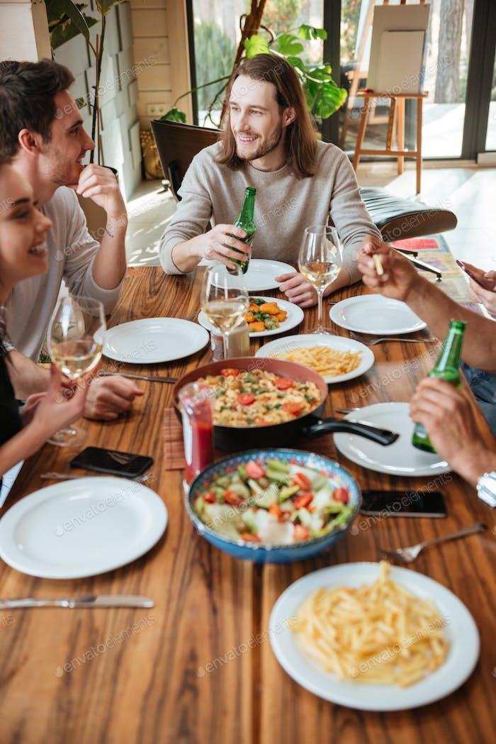 Gruppe von fröhlichen Freunden essen und reden am Tisch