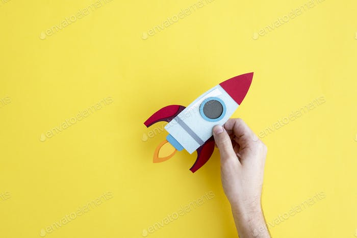 Hand Holding Rocket Spaceship on Yellow Background