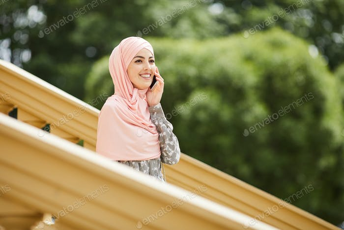 Happy Muslim woman talking on phone