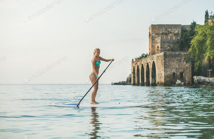Young beautiful slavian woman tourist practicing paddle boarding, Alanya