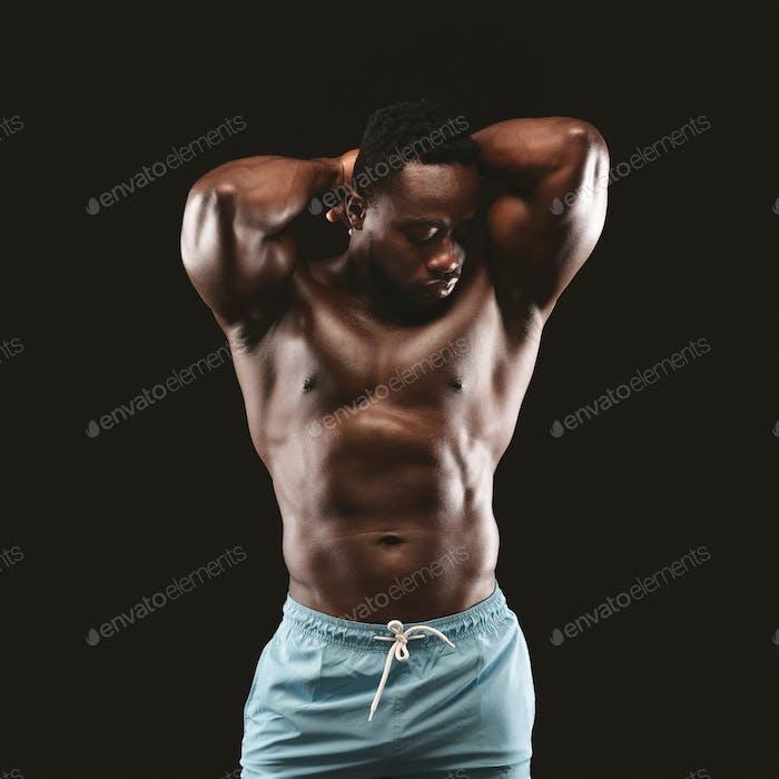 Portrait of hot black bodybuilder showing his muscles