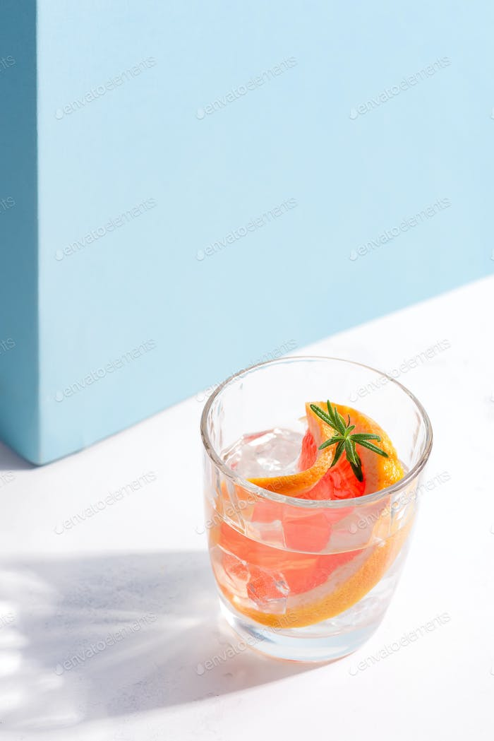 Refreshing cold summer drink in a glass with slice of grapefruit and ice cubes on a white table with