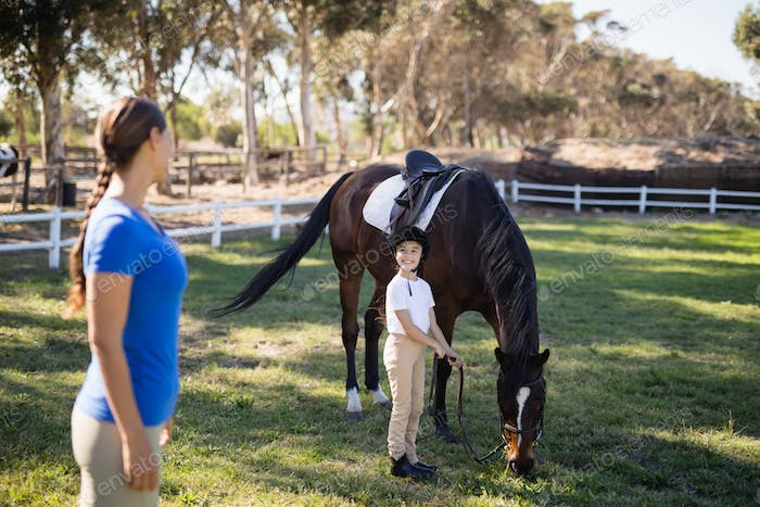 Side view of female jockey looking at sister standing by horse