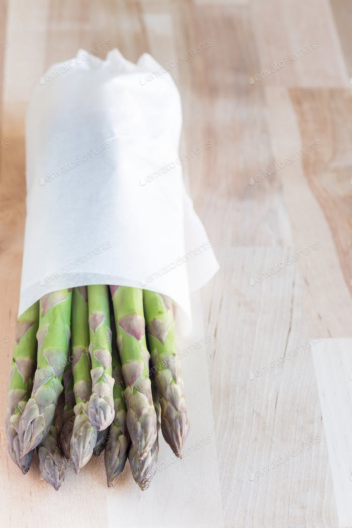 Bunch of fresh green asparagus on wooden table, vertical, copy s