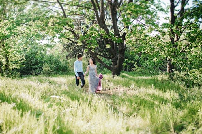ein Mann und ein Mädchen zu Fuß in den Frühlingsgarten der Flieder
