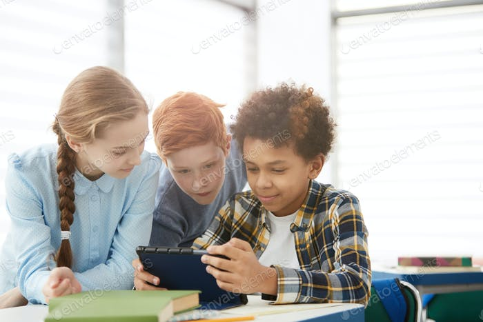 Group of Kids Using Tablet in School