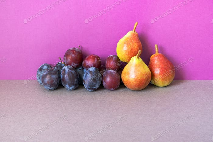 Still life composed of yellow red pears and blue plums.