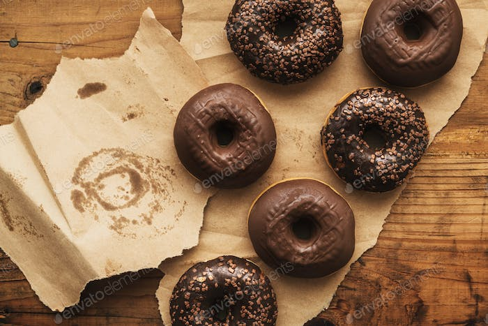 Tasty chocolate doughnuts with cream and crumbs