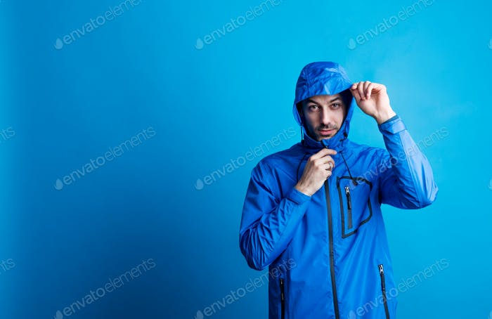 Portrait of a young man in a studio with anorak on a blue background.