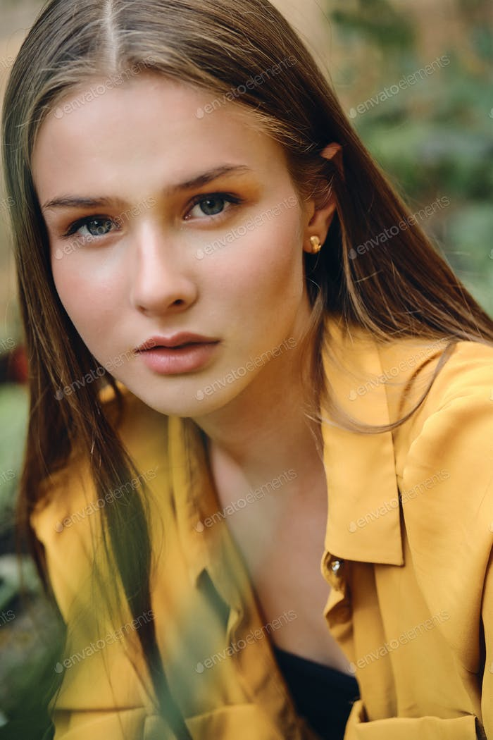 Beautiful pensive brown haired girl in yellow shirt dreamily looking in camera outdoor