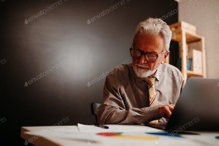 Elderly businessman works overtime in home office. Night work.