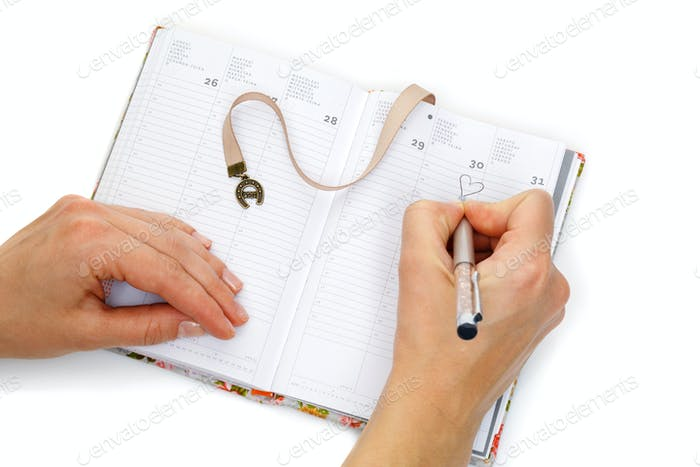 Notebook opened with female hands writing