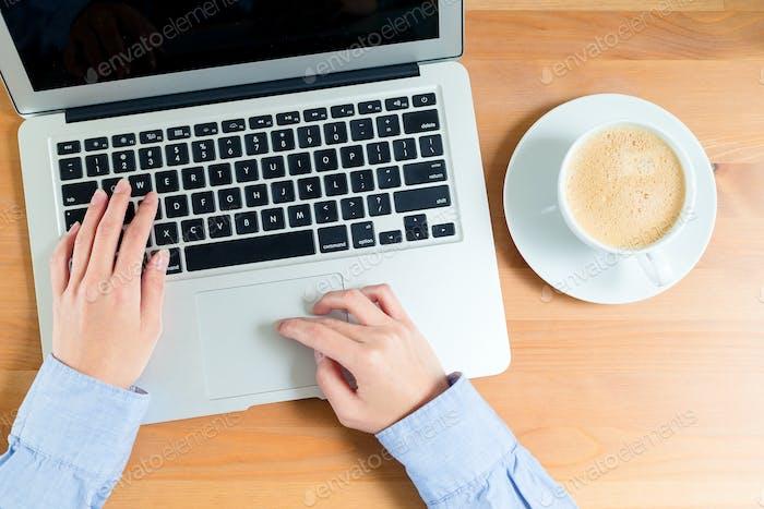 Mujer retorciendo en el ordenador portátil con café